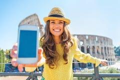 Femme montrant le téléphone portable devant le colosseum Photographie stock