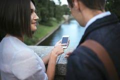 Femme montrant quelque chose à l'ami à son téléphone Images stock