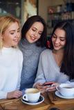 Femme montrant quelque chose sur le smartphone à deux amis Images libres de droits