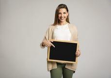 Femme montrant quelque chose sur un tableau Photos stock