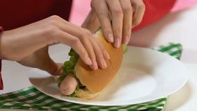 Femme mordant le hot-dog gras avec le ketchup, habitude alimentaire malsaine, aliments de préparation rapide banque de vidéos