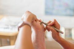 Femme morte de râpe de pied de solvant de peau de pédicurie dans le salon de clou Élimination des grains sur le pied avec un raso Image libre de droits