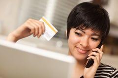 Femme multi-ethnique avec le téléphone, par la carte de crédit, ordinateur portatif Photographie stock