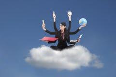 Femme multitâche d'affaires s'asseyant sur un nuage Image libre de droits
