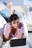 Femme multitâche parlant au téléphone utilisant l'ordinateur portatif images stock