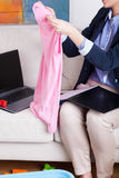 Femme multitâche travaillant à la maison et blanchisserie se pliante images stock