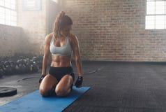 Femme musculaire établissant au centre de fitness Photographie stock libre de droits