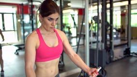 Femme musculaire d'athlète dans un dessus rose établissant dans les poids de levage de gymnase fille de forme physique s'exerçant banque de vidéos