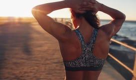 Femme musculaire dans le soutien-gorge de sports au coucher du soleil image libre de droits