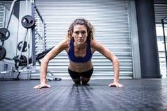Femme musculaire faisant des pousées Image stock