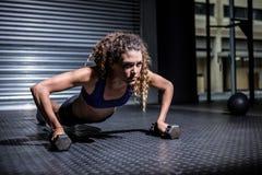 Femme musculaire faisant des pousées avec des kettlebells Images libres de droits