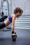 Femme musculaire faisant des pousées avec des kettlebells image libre de droits