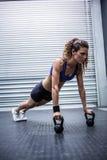 Femme musculaire faisant des pousées avec des kettlebells photographie stock libre de droits