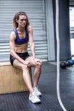 Femme musculaire focalisée s'asseyant sur une boîte photo stock