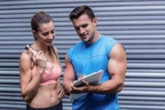 Femme musculaire observant ses résultats sur le presse-papiers images stock