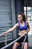 Femme musculaire s'exerçant avec la corde image stock