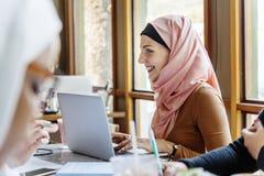 Femme musulmane à l'aide de l'ordinateur portable au cours de la réunion Image libre de droits