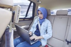 Femme musulmane à l'aide de l'ordinateur portable dans la voiture Image libre de droits