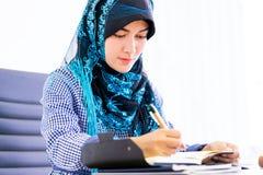 Femme musulmane à l'aide du comprimé numérique sur la table de bureau photographie stock libre de droits