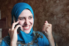 Femme musulmane arabe heureuse avec le mobile Photo libre de droits