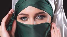 Femme musulmane asiatique en gros plan avec le voile traditionnel de hijab d'isolement au-dessus du fond noir clips vidéos