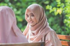 Femme musulmane assez asiatique en café avec l'ami Images stock