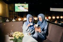 Femme musulmane assez jeune avec une tasse de café ou de thé dans l'action Photos stock