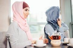 Femme musulmane assez jeune avec une tasse de café ou de thé dans l'action Images stock