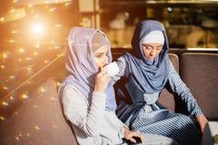 Femme musulmane assez jeune avec une tasse de café ou de thé dans l'action Photos libres de droits