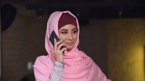 Femme musulmane attirante dans le hijab parlant au téléphone portable Photos libres de droits