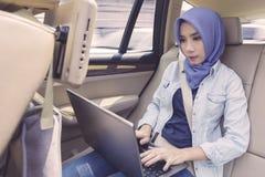 Femme musulmane avec l'ordinateur portable dans la voiture Images libres de droits
