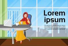 Femme musulmane d'affaires dans des vêtements traditionnels fonctionnant à l'ordinateur portable dans le bureau moderne Photos stock