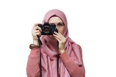 Femme musulmane dans le hijab prenant la photo par l'appareil-photo de slr de vintage Photographie stock