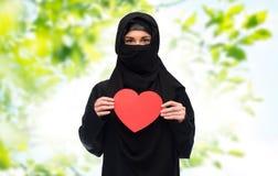 Femme musulmane dans le hijab tenant le coeur rouge Photos libres de droits
