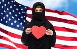Femme musulmane dans le hijab tenant le coeur rouge Photo libre de droits