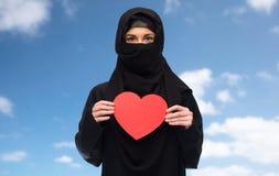Femme musulmane dans le hijab tenant le coeur rouge Photo stock