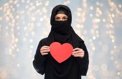 Femme musulmane dans le hijab tenant le coeur rouge Photos stock