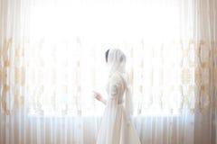 Femme musulmane dans un foulard blanc se tenant à la fenêtre image libre de droits