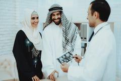 Femme musulmane de grossesse heureuse avec le mari arabe photo stock