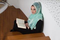 Femme musulmane lisant le Quran islamique saint de livre photographie stock libre de droits