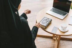 femme musulmane moderne avec le livre de quran et les dispositifs numériques photographie stock