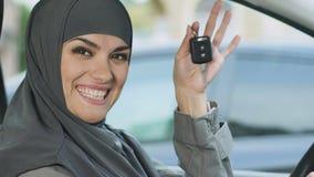 Femme musulmane montrant des clés, excitées avec l'achat de voiture, conduisant l'égalité entre les sexes banque de vidéos