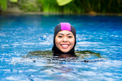 Femme musulmane portant des vêtements de bain de Burkini dans la piscine Photographie stock