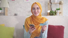 Femme musulmane positive de portrait jeune dans le hijab souriant tenant le smartphone et carte de banque se reposant sur le sofa banque de vidéos