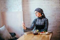 Femme musulmane prenant le selfie en café avec le smartphone image stock