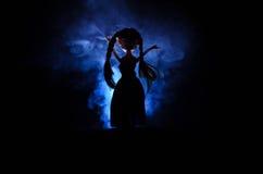 Femme mystérieuse, scène d'horreur de femme effrayante de poupée de fantôme sur le fond bleu-foncé avec de la fumée Image libre de droits