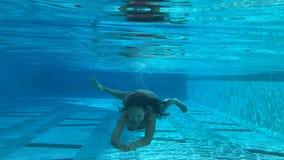 Femme nageant sous l'eau dans une piscine bleue banque de vidéos