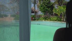 femme naturelle regardant la piscine du balcon de luxe de costume tenant les rideaux appréciant la fuite d'été à l'hôtel de luxe clips vidéos