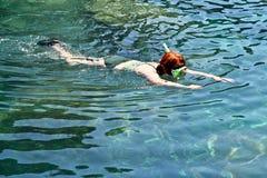 Femme naviguant au schnorchel dans un bassin naturel Photographie stock libre de droits