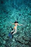 Femme naviguant au schnorchel en eau de mer verte photos libres de droits
